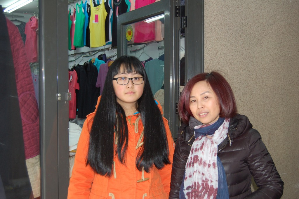 Zirui Yu et sa mère, devant l'enseigne familiale. La jeune adolescente veut construire sa vie à Belgrade.